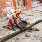 La mujer intenta encontrar el polvo de oro en la canalización Imagen de archivo libre de regalías
