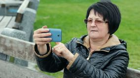 La mujer intenta hacer el selfie y es muy feliz sobre él Morenita adulta divertida con un smartphone en sus manos almacen de metraje de vídeo