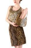 La mujer irreconocible se vistió en la falda y la blusa del estampado de animales, sosteniendo un bolso. Foto de archivo