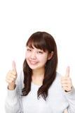 La mujer japonesa joven con los pulgares sube gesto Imagen de archivo