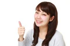 La mujer japonesa joven con los pulgares sube gesto Fotografía de archivo