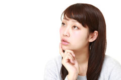 La mujer japonesa joven piensa en algo Fotos de archivo