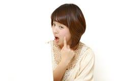 La mujer japonesa joven se preocupa de piel áspera seca Imagenes de archivo