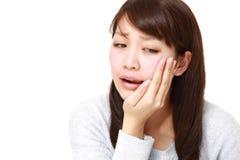 La mujer japonesa joven sufre de dolor de muelas Foto de archivo libre de regalías