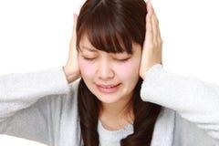 La mujer japonesa joven sufre de ruido Fotografía de archivo libre de regalías