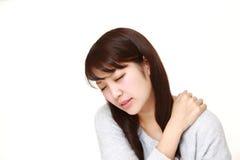 La mujer japonesa joven sufre del dolor del cuello Imagen de archivo libre de regalías