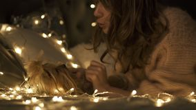 La mujer joven abraza y besa su perro rodeó luces de la Navidad en cama almacen de metraje de vídeo