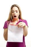 La mujer joven abre el bolso con sorpresa Fotografía de archivo libre de regalías