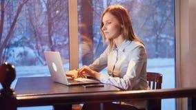 La mujer joven abre el ordenador portátil y comienza a mecanografiar cerca de ventana panorámica 4K almacen de video