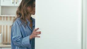 La mujer joven abre el refrigerador metrajes