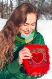 La mujer joven abre una caja roja con el corazón y la sonrisa Imagenes de archivo