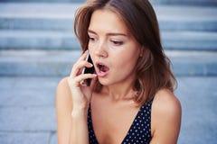 La mujer joven abrió su boca en el asombro mientras que hablaba en t imagen de archivo libre de regalías