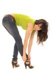 La mujer joven abrocha su zapato Imagen de archivo