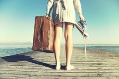 La mujer joven acaba de llegar al destino con su maleta Imagen de archivo libre de regalías