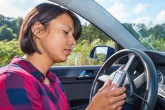 La mujer joven actúa al planificador electrónico de la ruta en coche foto de archivo