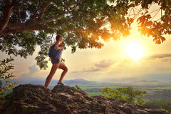 La mujer joven admira la puesta del sol con una mochila que se coloca en el acantilado Foto de archivo