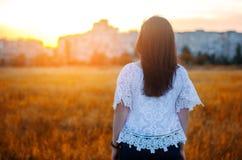 La mujer joven admira la puesta del sol detrás ve outdoor Verano compita Fotos de archivo