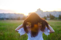 La mujer joven admira la puesta del sol detrás ve outdoor Verano compita Imagen de archivo