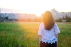 La mujer joven admira la puesta del sol detrás ve outdoor Verano compita Fotos de archivo libres de regalías