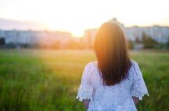 La mujer joven admira la puesta del sol detrás ve outdoor Verano compita Imagen de archivo libre de regalías
