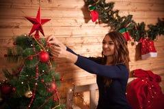 La mujer joven adorna en el árbol de navidad Imagenes de archivo