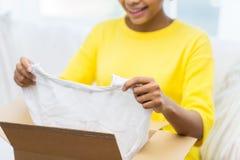 La mujer joven africana feliz con el paquete encajona en casa Foto de archivo