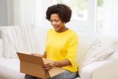 La mujer joven africana feliz con el paquete encajona en casa Imágenes de archivo libres de regalías