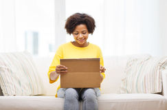 La mujer joven africana feliz con el paquete encajona en casa Fotos de archivo libres de regalías