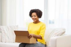 La mujer joven africana feliz con el paquete encajona en casa Imagenes de archivo
