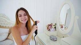 La mujer joven agraciada apila el pelo usando el pelo de Styler del pelo, sentándose en silla fotos de archivo libres de regalías