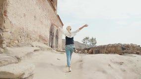 La mujer joven agradable con el pelo rubio camina con confianza hacia flujo del fuerte viento metrajes