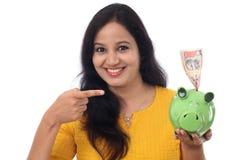 La mujer joven ahorra el dinero en la hucha Fotos de archivo