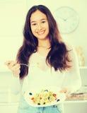 La mujer joven alegre almuerza en casa Imagen de archivo libre de regalías