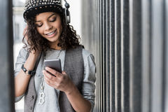 La mujer joven alegre del inconformista se está colocando con smartphone al aire libre Foto de archivo
