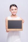 La mujer joven alegre en la tenencia blanca de la camiseta firma encima el fondo gris Fotos de archivo