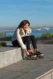 La mujer joven alegre es relajante después de rollerblading Fotos de archivo