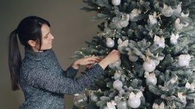 La mujer joven alegre está adornando el árbol del Año Nuevo con las bolas de plata elegantes y las luces de oro que disfruta de a almacen de video