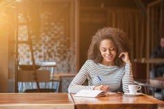 La mujer joven alegre está escribiendo en cuaderno Imagenes de archivo
