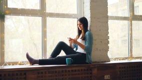 La mujer joven alegre está utilizando el smartphone que se sienta en travesaño de la ventana con la taza de té que se relaja en c almacen de video