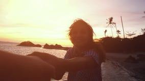 La mujer joven alegre lleva a cabo la mano de su amigo y tienta el suyo a los paseos a lo largo de la playa durante puesta del so metrajes