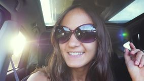 La mujer joven alegre lleva las gafas de sol que se sientan en pasajero del coche y canción del canto en la cámara lenta con el l almacen de video