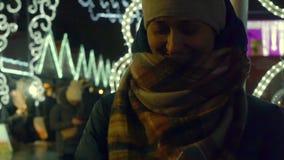 La mujer joven alegre ríe y pone guantes en invierno escarchado en la calle almacen de metraje de vídeo