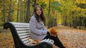 La mujer joven alegre se sienta con un manojo de hojas, de sonrisas, y de frolicks almacen de metraje de vídeo