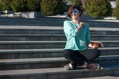 La mujer joven alegre se sienta en los pasos en el parque y las medidas él Fotos de archivo