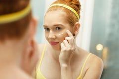 La mujer joven aplica la crema antienvejecedora que mira el espejo Imagen de archivo