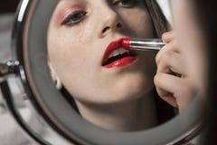 La mujer joven aplica el lápiz labial rojo en espejo del maquillaje Foto de archivo