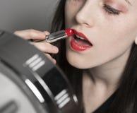 La mujer joven aplica el lápiz labial rojo en espejo del maquillaje Imagen de archivo