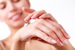 La mujer joven aplica la crema en sus manos Imagen de archivo