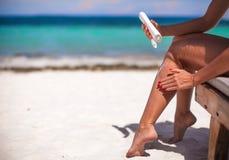La mujer joven aplica la crema en sus piernas bronceadas lisas Fotos de archivo libres de regalías