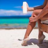 La mujer joven aplica la crema en sus piernas bronceadas lisas Imagenes de archivo